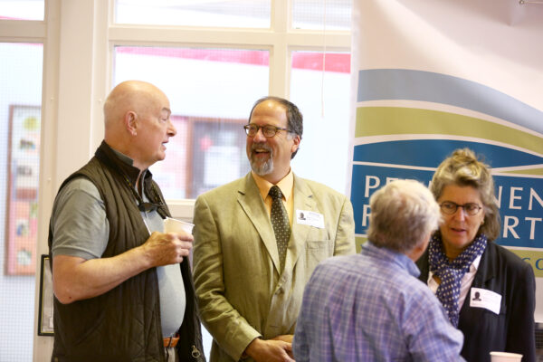 Paul Karasik, center, converses with Edward Miller, left, at a recent Scholarship Reception.